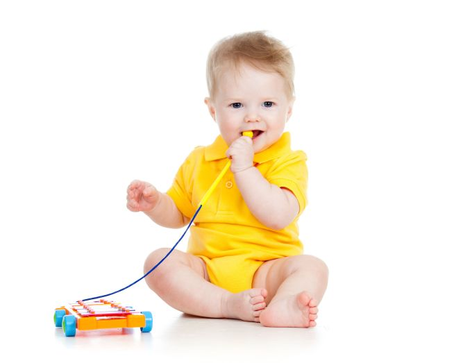 34186946 - baby boy playing with musical toy isolated